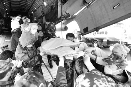 飞机降落后,等待在候机大厅外的一排救护车闪着警灯,排队将12名重