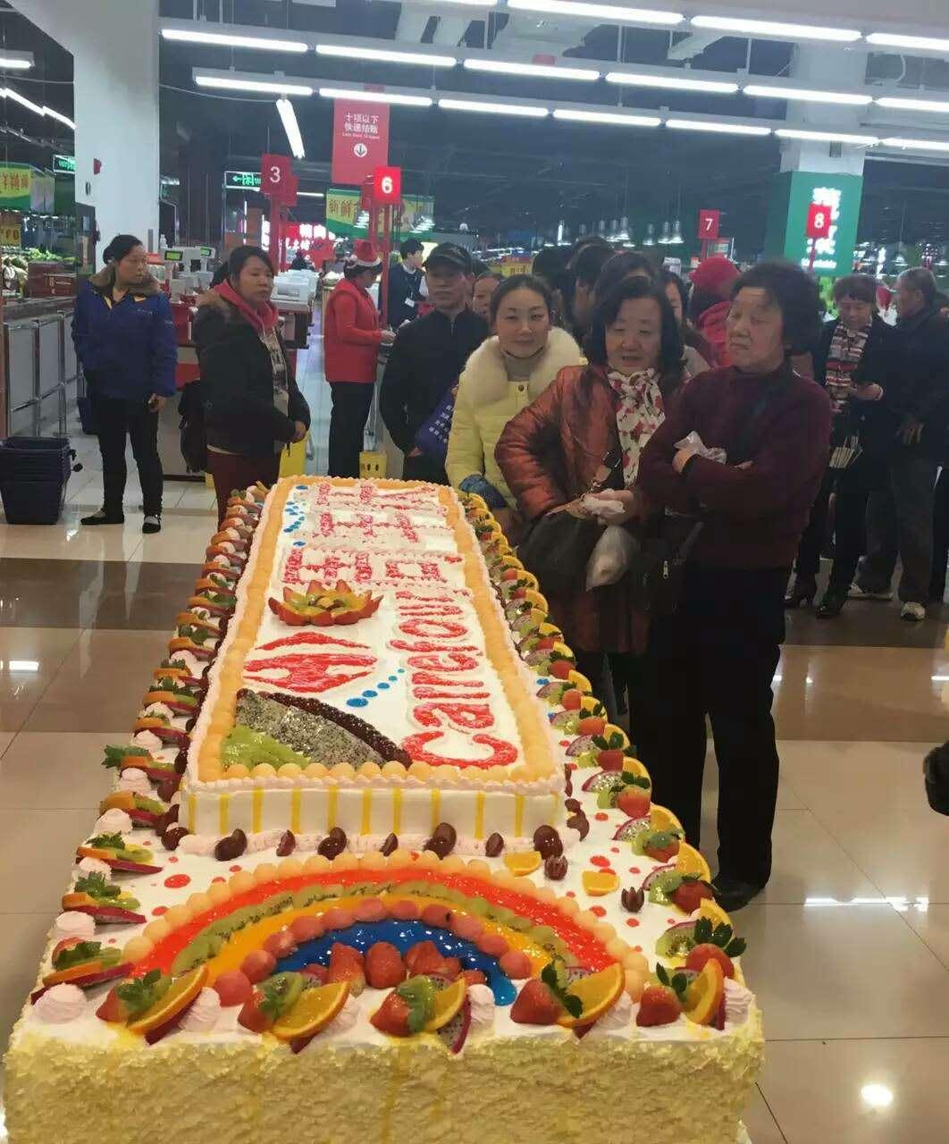 12月23日,一个长5米,宽1米的精心制作的大奶油蛋糕出现在武汉家乐福超市南湖武昌府店,据介绍,这个全长为3米的蛋糕是由6个面包师耗时6小时,耗近20公斤面粉、500个鸡蛋及10多斤的各种辅料制作完成。 据了解,这是为了庆祝武汉家乐福南湖武昌府一周年庆所举行的义卖活动,活动的目的是 为了让大家共同参与家乐福的暖冬行动。 在蛋糕义卖活动现场可以看到,不到20分钟,刚出炉的蛋糕就被消费者抢购一空,当得知这些蛋糕卖出的钱是要全数捐给慈善机构的,大家纷纷拿出3块钱或者5块钱买上一块蛋糕,一些市民表示,参