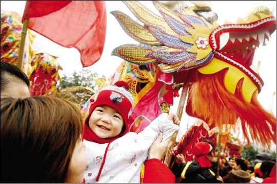 昨日,一位近两岁的小朋友看到舞龙开心的笑.本报记者 原丽阳 摄图片