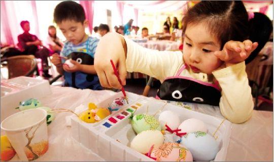一位正在绘彩蛋的小女孩姿态优雅.武汉新天地,100位3至5岁 高清图片