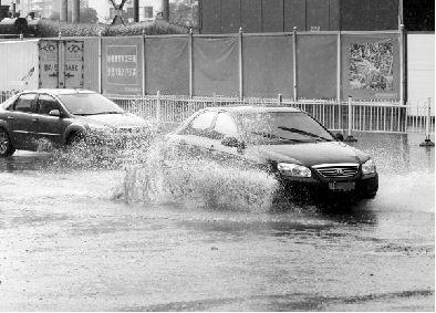 昨日,汽车经过积水的路面溅起水花.本报记者 张朋 摄