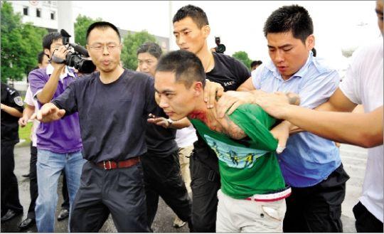 警方/昨日,嫌疑人(绿衣者)被警方制服。CFP图