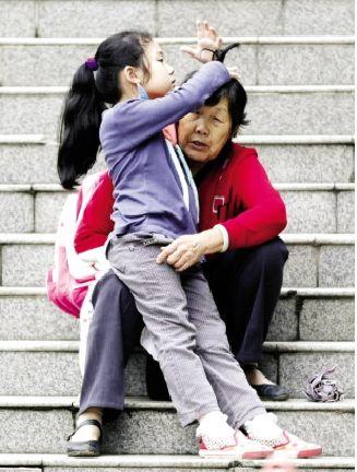 一位刚放学的小女孩坐在奶奶的腿上试着给短发的奶奶扎辫子改造型.