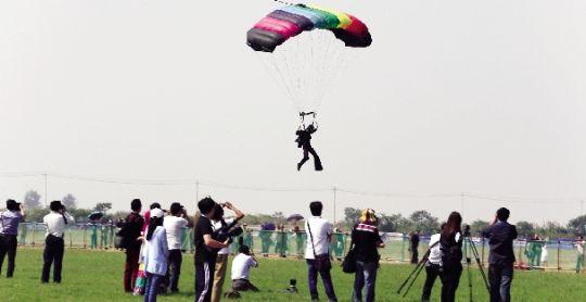 昨日,跳伞运动员在高空完成指定动作后降落到安全地点,不少市民在一旁