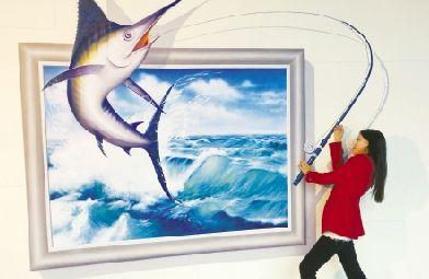 东湖海洋世界里,墙上的3d画栩栩如生,一位女子做出正在钓鱼的